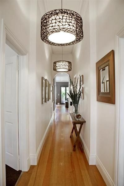 narrow hall table matching frames and repeating light fixtures image hallway lighting