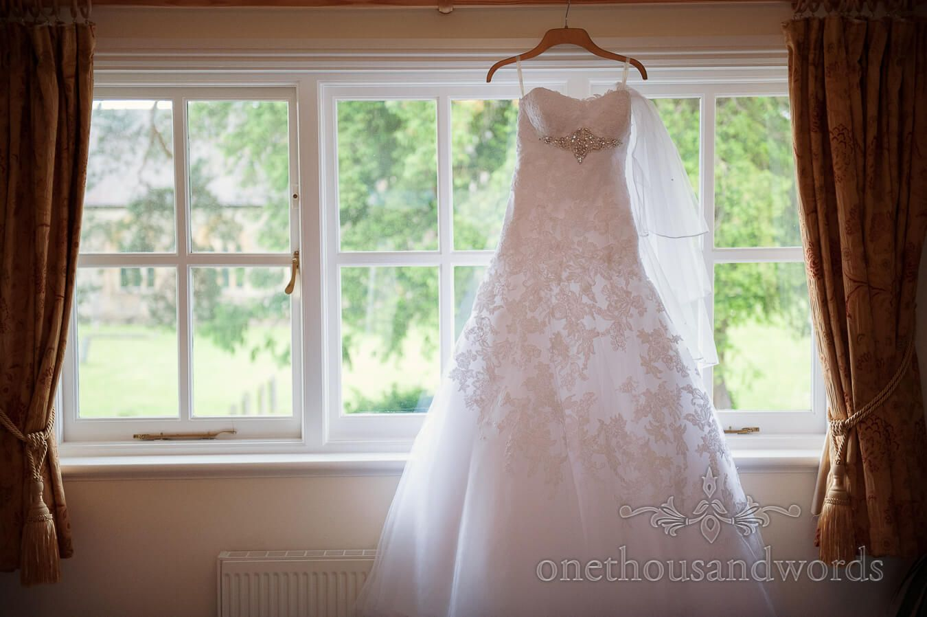 country themed wedding dresses Backlit wedding dress hangs in window at Country Theme Wedding Photography by one thousand words