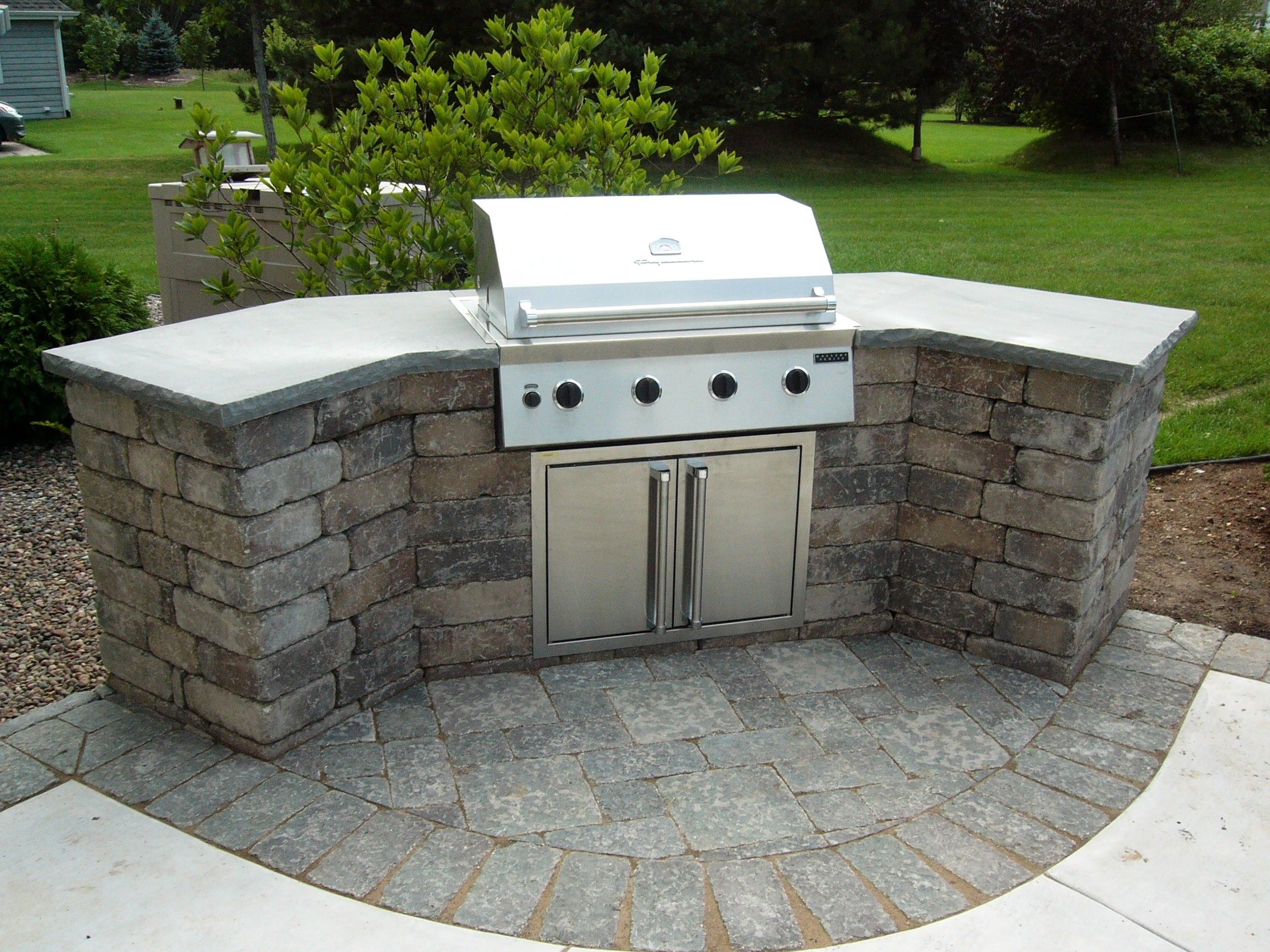 outdoor kitchen island Curved Stone Prefab Kitchen Island With Gray Concrete Countertop And Barbeque Grill On Backyard Garden