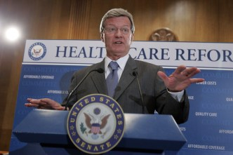 Senator Max Baucus in front of a health care banner.
