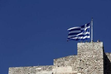 Tourists stand under a Greek national flag atop the Acropolis hill in Athens, June 14, 2015. REUTERS/Kostas Tsironis