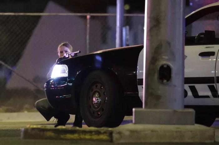 Policial se protege atrás de viatura da polícia no momento em que tiros são ouvidos perto do resort e casino Mandalay Bay, em Las Vegas Strip (Foto: John Locher/AP)