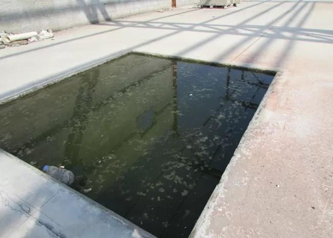 Fosso que vai alimentar a esteira elevada acumula água em obra parada da Central de Triagem de Bangu (Foto: Janaína Carvalho / G1)