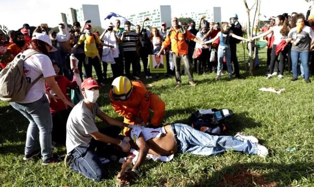 Um paramédico ajuda um homem ferido durante protesto contra o presidente Michel Temer, em Brasília  (Foto: Ueslei Marcelino/Reuters)