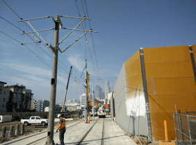 Installation of overhead power system and noise barrier along shoofly track.