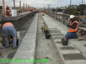 Finish work to remove surface irregularities following plinth form removals on Aviation/Century Bridge.