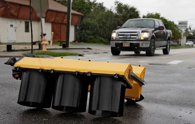 Algunos automóviles se detienen ante un semáforo derribado por el huracán en Cocoa Village (AP Photo/Chris O'Meara)