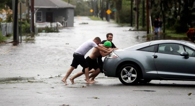 Noah Simons empuja a su auto, que había sido arrastrado por las inundaciones en Daytona Beach (AP Photo/Eric Gay)