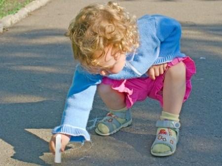 Little girl drawing with sidewalk chalk