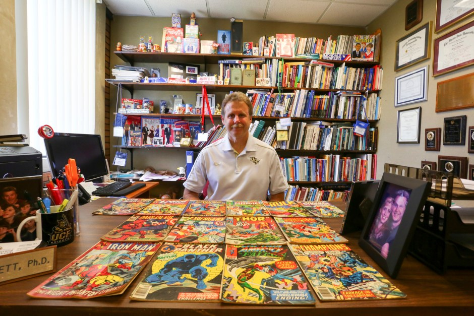 Political science professor Aubrey Jewett with some of his collection of superhero comics. (Photo via University of Central Florida)