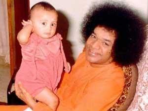 Photo of Sathya Sai Baba holding a baby