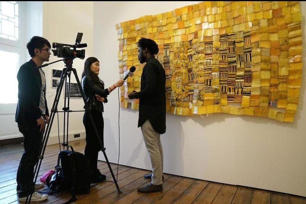 Le Ghanéen Serge Attukwei Clottey, en interview devant l'un de ses pagnes faits de plastique récupérés - Packed Community, 2016. © Courtesy of the artist and Gallery 1957