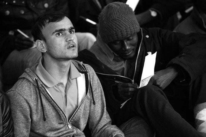 En plein air, dans Paris, des migrants suivent un cours de français, photo - Éric Coquelin