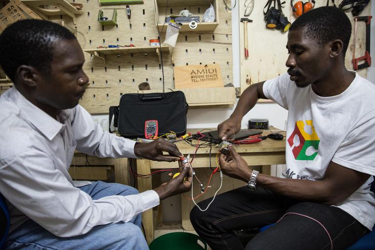 Modou et Djouri sont en train de câbler quelques LEDs. CRÉDITS : MATTEO MAILLARD