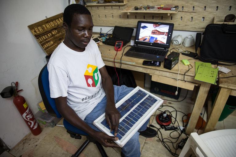 Modou présente son panneau solaire domestique fabriqué de toute pièce dans son « fab lab ». CRÉDITS : MATTEO MAILLARD