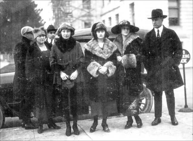 Policewoman Kate O'Conner, victims Jessie Montgomery, Pearl Hanley, Edna Fulmer and San Francisco Detective Lester Dorman stand alongside the police car parked next to the Sonoma County Courthouse. The two men in the background are unidentified. December 5, 1920