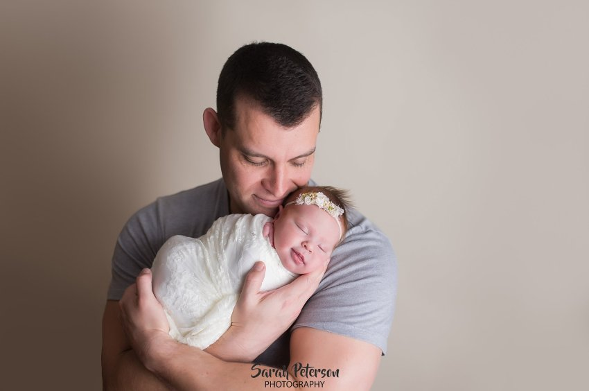 Dad holding baby girl while she is smiling