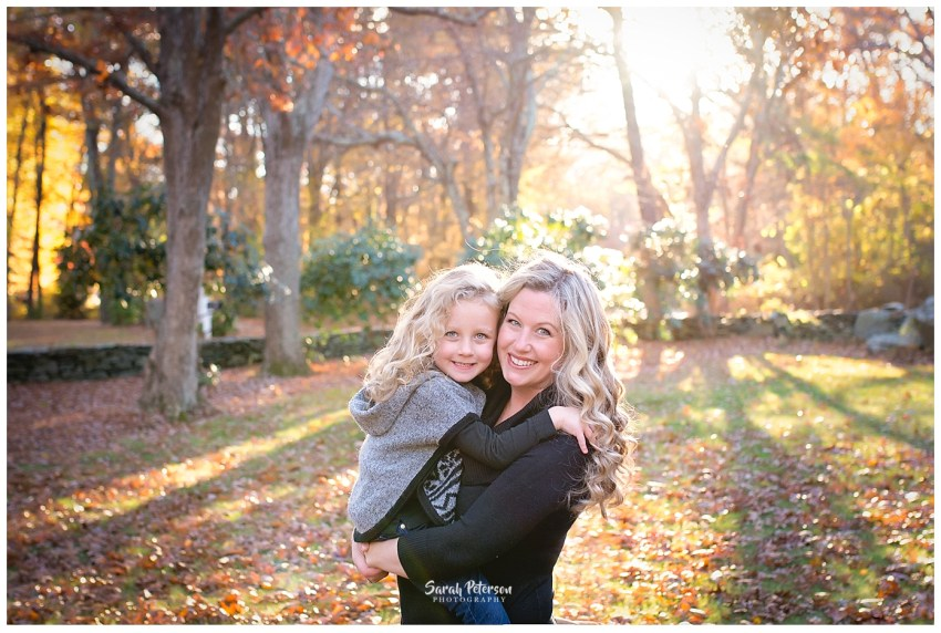 Sarah Peterson holding daughter in the fall leaves with sunset behind them