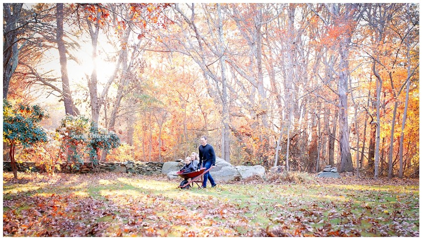Dad rolling kids in a wheel barrow in the fall, colored leaves.