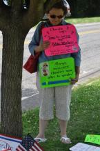A woman protests Governor Christie's pension payment walk-back at his 6/25/14 Haddon Heights Town Hall (photo credit: Alyssa LaFage)