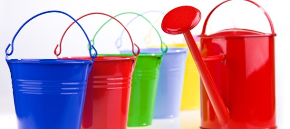 Five coloured buckets in one diagonal line with red watering can
