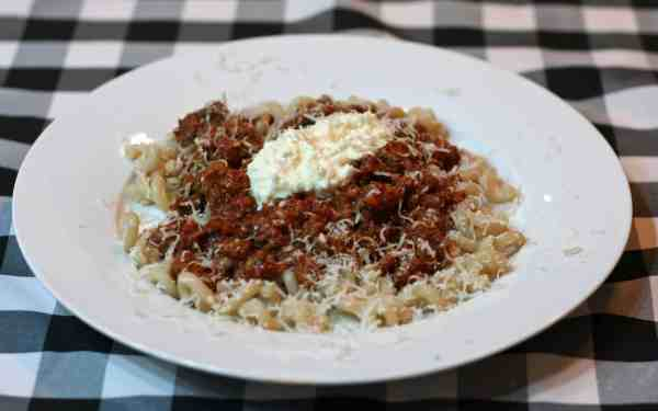 Spaghetti Bolognese served over gluten free pasta or and garnished with ricotta.