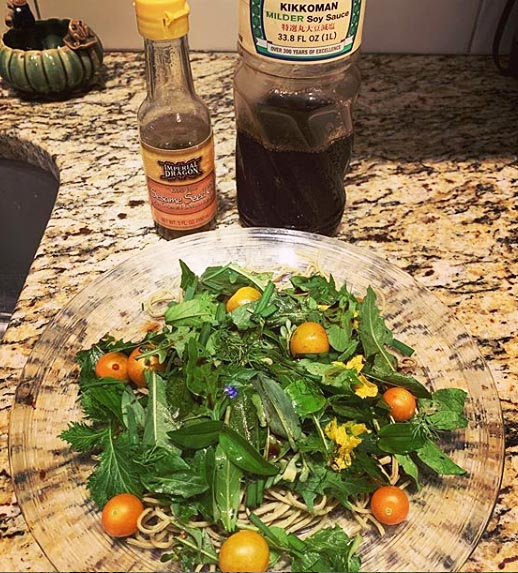 Fresh picked salad from the backyard with cherry tomatoes, dill, arugula, chives, romaine, mustard greens, edible flowers and wild greens.
