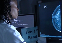 A nurse looking at a mammogram
