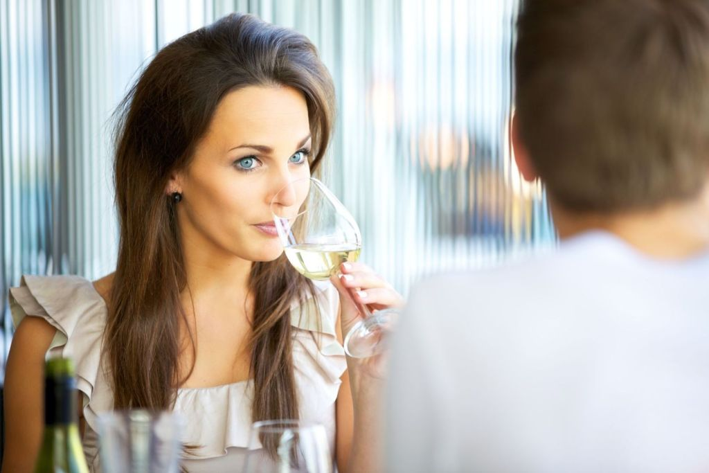 13518947 - portrait of an attractive woman drinking wine while on a date with her boyfriend