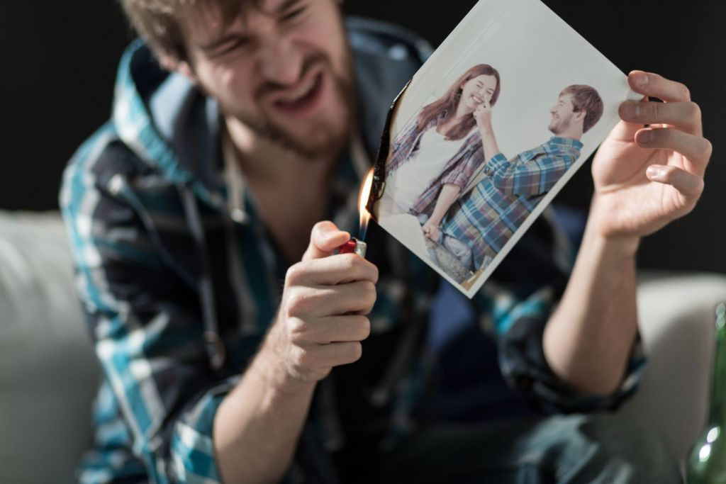 39054823 - angry young man burning photo with ex-girlfriend