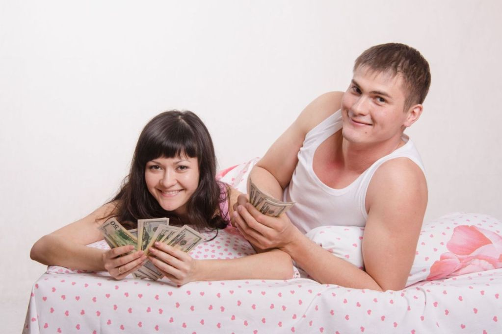 28020724 - young couple with money lying in bed