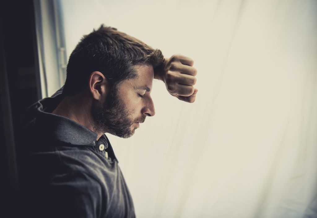 31417076 - young attractive man leaning desperate on window glass at home, looking worried, depressed, thoughtful and lonely suffering depression in work or personal problems concept with copy space