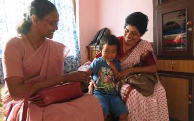 Sisters visit with young girl, an earthquake survivor
