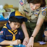 Bay-Lakes Council executive board vice president Lucia Cronin works with Cub Scout Josh Garcia of Pack 3817.