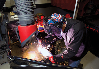 Adult leaders practice the welds they will soon teach Scouts.
