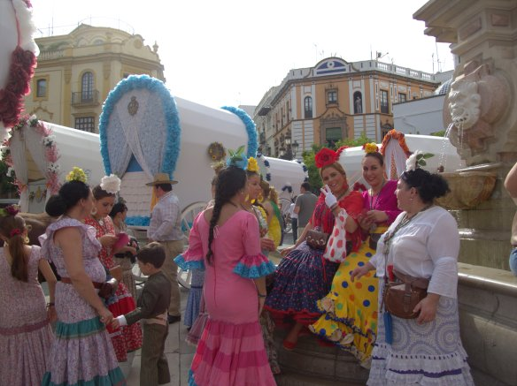A colourful romeria scene - girls with their carrozas and bright dresses in the plaza in front of the Giralda.