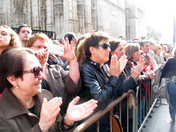Sevillanos applauding as the funeral cortege passes on the way to the cathedral.