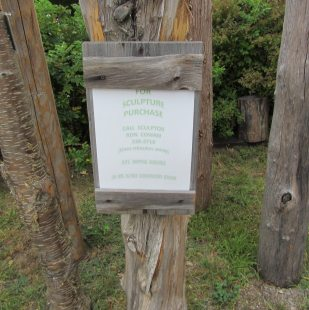 Wooden sign with contact details for scupture purchases.