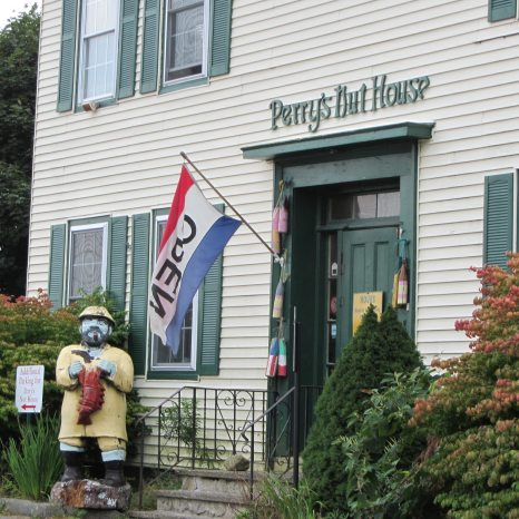 Large yellow building houses Perry's Nut house with a wooden lobsternan out front to greet customers.