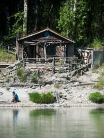 A young man looks at rocks along the banks of the Cowlitz River in front of what appeared to be a fishing shack south of Castle Rock on Wednesday, June 17, 2015.