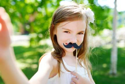 Adorable little girl playing with paper moustache on a stick