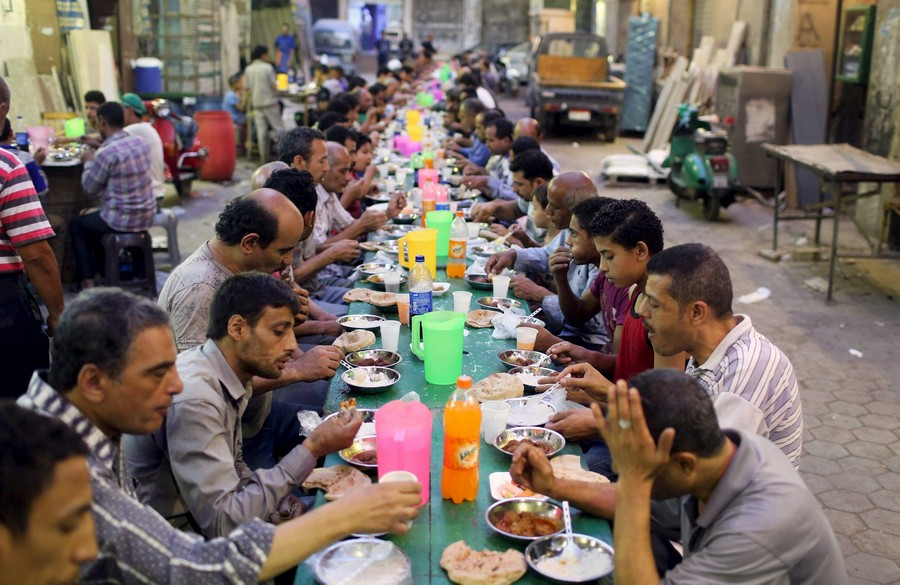 People eat their Iftar meal at charity tables that offer free food during the holy fasting month of Ramadan in Cairo