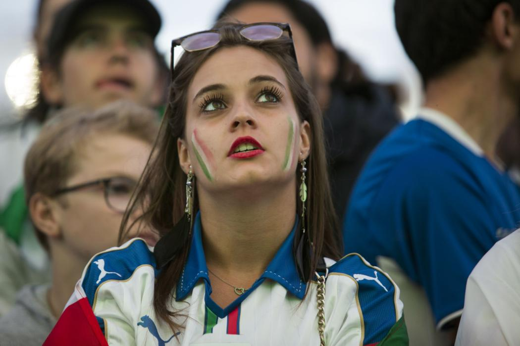 An Italia's supporter reacts as she watches on a giant screen in a fan zone the Euro 2016 quarter final football match between Italy and Germany on July 2, 2016, in Paris. / AFP PHOTO / GEOFFROY VAN DER HASSELT