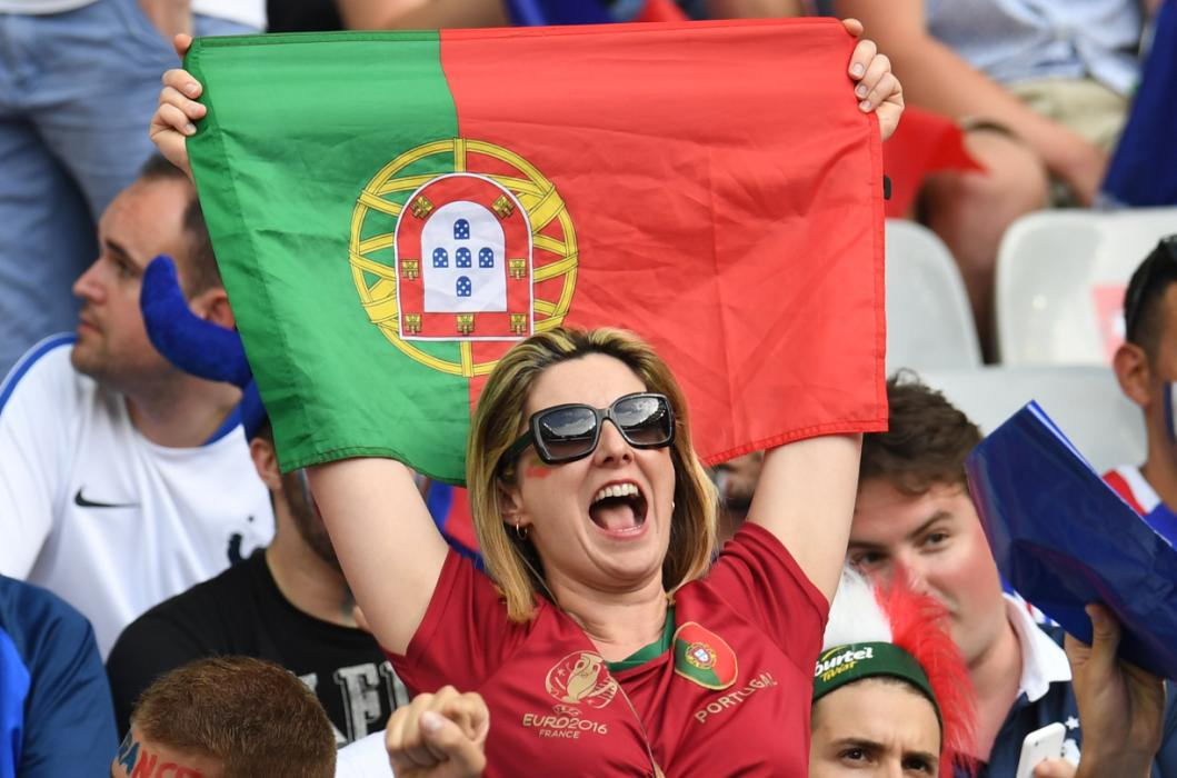 A Portugal supporter cheer ahead of the Euro 2016 final football match between Portugal and France at the Stade de France in Saint-Denis, north of Paris, on July 10, 2016. / AFP PHOTO / PATRIK STOLLARZ