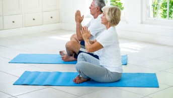Senior couple meditating on exercise mat