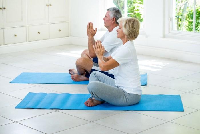Senior couple meditating on exercise mat
