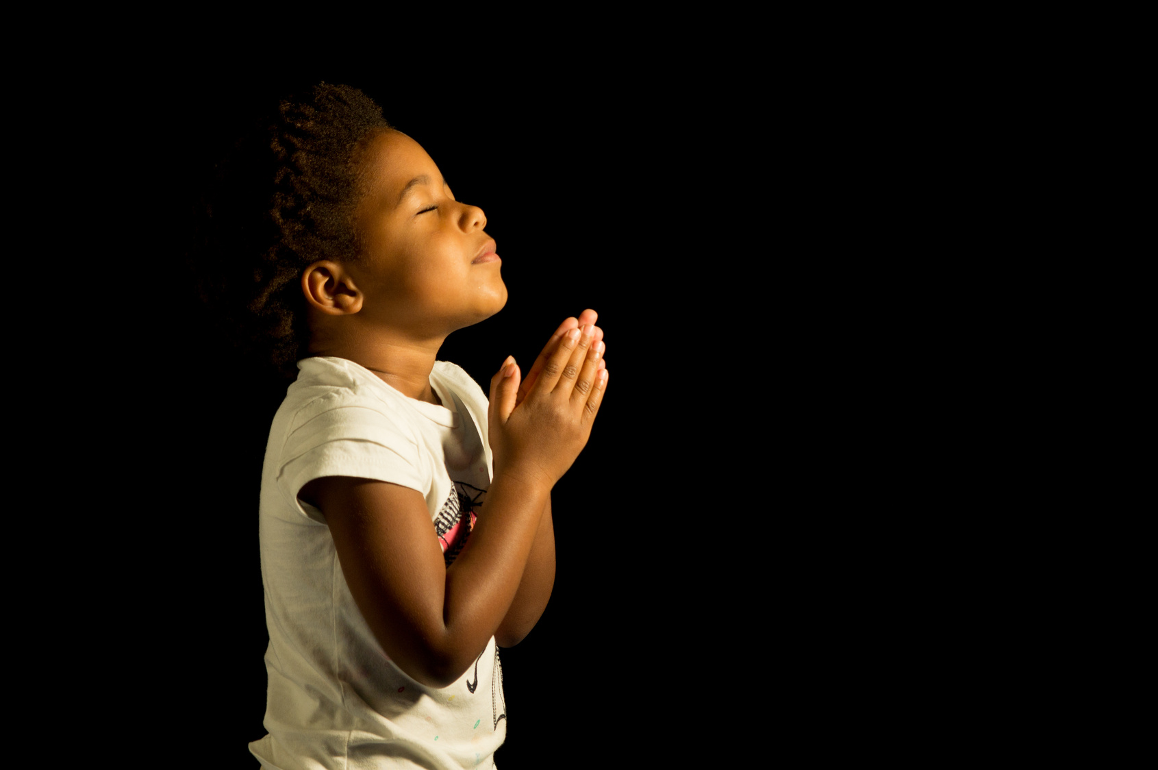 A young child prays to God.