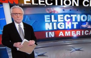 Wolf Blitzer hasn't moved since November 2012. He's still standing in front of that screen, interviewing imaginary holograms about Iowa and California.