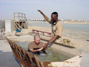 040415-N-6419K-011 Iraq (Apr. 15, 2004) - U.S. Navy Chaplain, Lt. Cmdr. Lulrick Balzora, assigned to Naval Mobile Construction Battalion Fourteen (NMCB-14), prepares to baptize Construction Mechanic Kyle Ellis. Balzora baptized several members assigned to NMCB-14 and NMCB-74 using a 2.5 cubic yard front-end loader bucket as an improvised baptismal. NMCB-14 and NMCB-74 are currently deployed in Iraq supporting Operation Iraqi Freedom (OIF). U.S. Navy photo by Builder 2nd Class Jerome Kirkland (RELEASED)