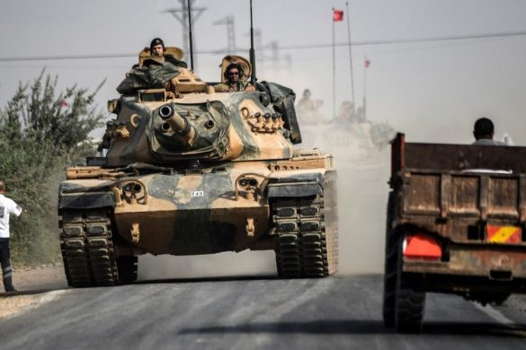 This picture taken around 5 kilometres west from the Turkish Syrian border city of Karkamis in the southern region of Gaziantep, on August 25, 2016 shows a civil truck passing by Turkish Army tanks driving to the Syrian Turkish border town of Jarabulus. Turkey's army backed by international coalition air strikes launched an operation involving fighter jets and elite ground troops to drive Islamic State jihadists out of a key Syrian border town. The air and ground operation, the most ambitious launched by Turkey in the Syria conflict, is aimed at clearing jihadists from the town of Jarabulus, which lies directly opposite the Turkish town of Karkamis. / AFP PHOTO / BULENT KILIC